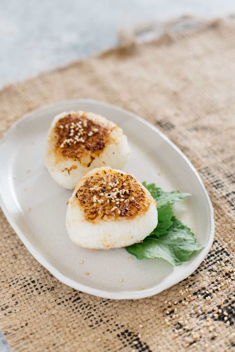 two miso glazed rice balls on an oval plate
