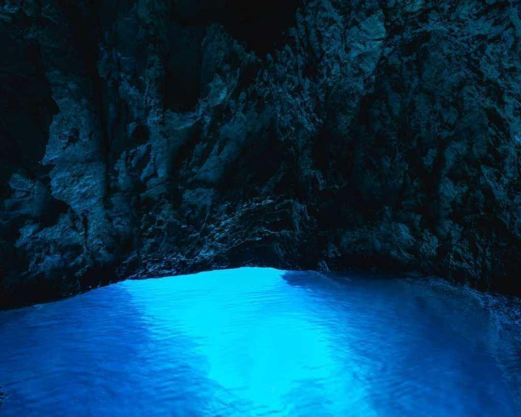 Wpadające światło tworzy poświatę w błekitnej jaskini na wyspie Biševo