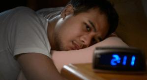 man lying on bed lookin at the digital clock