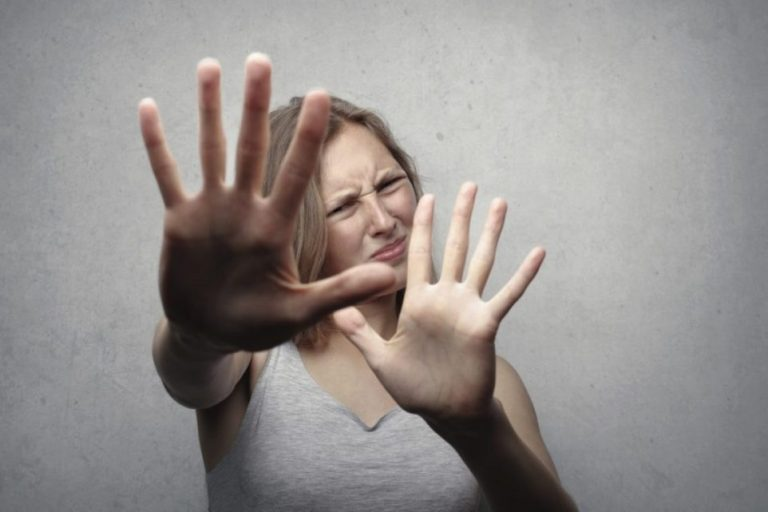 A lady with hands up fearing change.