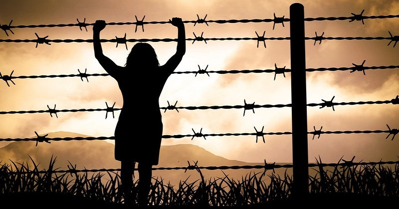 Person outside wire fence, signifying victim mentality