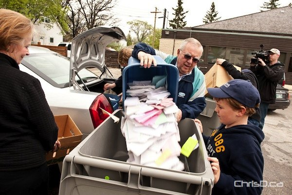Walter Schurko empties his personal documents to be shredded during last year's Free Personal Shred Day event on Henderson Highway. (TED GRANT / CHRISD.CA)