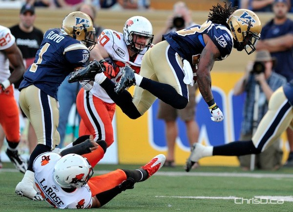 Winnipeg Blue Bombers' Jonathan Hefney (23) leaps over BC Lions' J.R. LaRose during the first half of their CFL game in Winnipeg on Thursday, July 28, 2011. (FRED GREENSLADE / REUTERS)