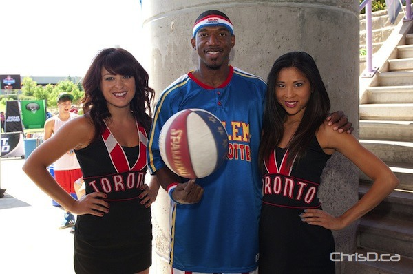 "Anthony ""Buckets"" Blakes of the Harlem Globetrotters effortlessly spins a basketball on his finger, while joined by two members of the Toronto Raptors Dance Pak at the NBA Jam Session on Saturday, August 13, 2011. (TED GRANT / CHRISD.CA)"