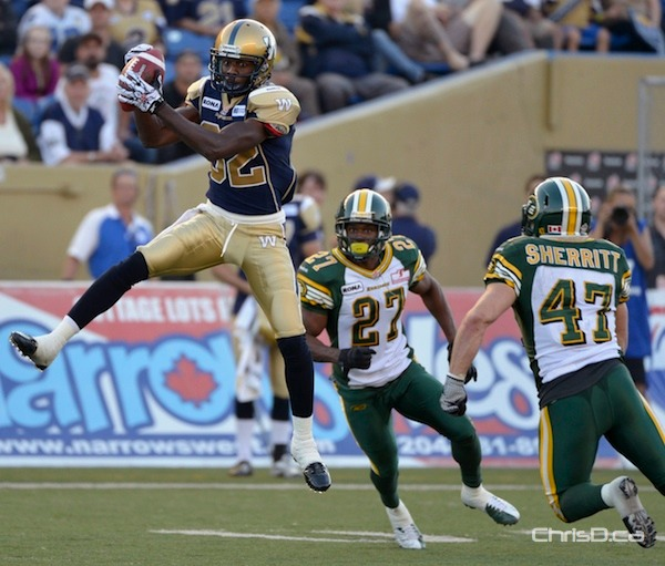 Winnipeg Blue Bombers' slotback Terrence Edwards (L) makes a catch as Edmonton Eskimos' Ronnie Prude (C) and JC Sherritt defend during the first half of their game at Canad Inns Stadium in Winnipeg on Thursday, July 26, 2012. (FRED GREENSLADE / REUTERS)