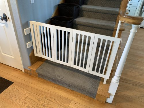 Folding dog gate extended across the bottom of the stairway