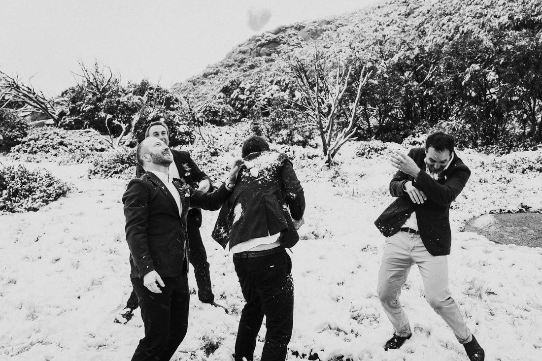 Groomsmen having a snowball fight by Mt Beauty wedding photographer