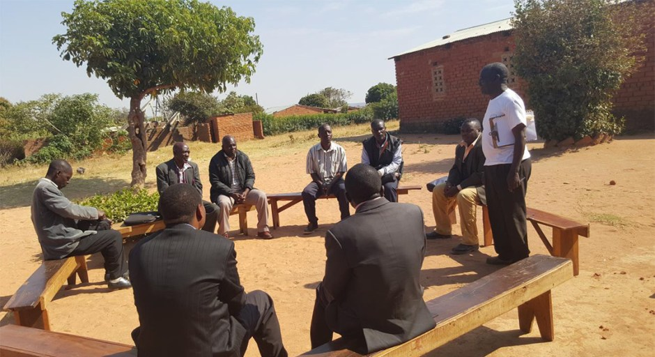 African man teaching students in open air.