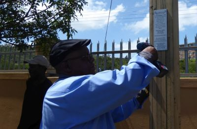 Pastor Lulama Dick attaching the plaque