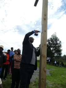 Reverend Makoko attaching plaque