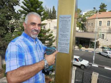 Pastor Nizar securing plaque