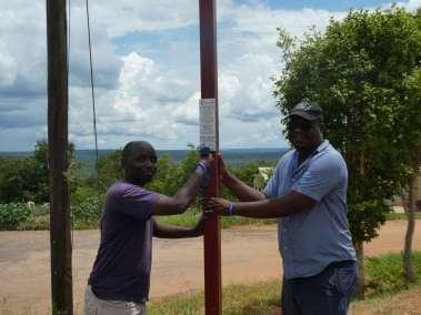 Pastor Moyo Attaching Plaque Declaring Gods Glory