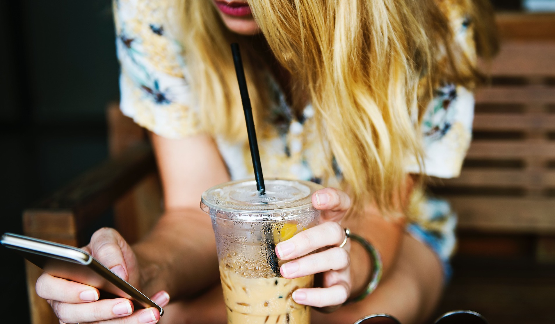blonde girl with phone and iced coffee