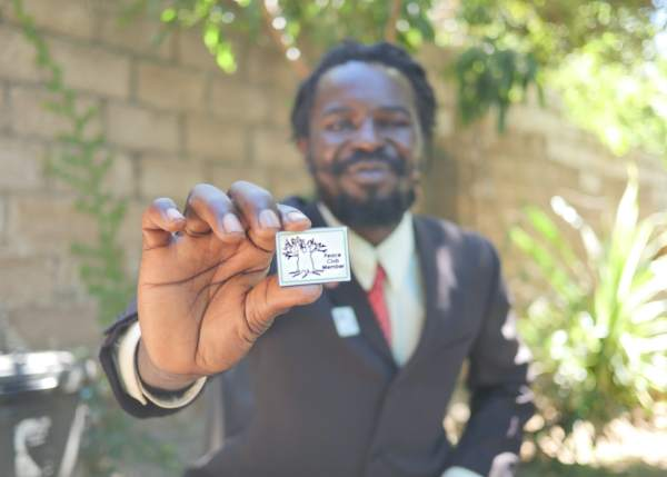 Zebron Mwale holds his badge to signify his Peace Club membership in April 2021.