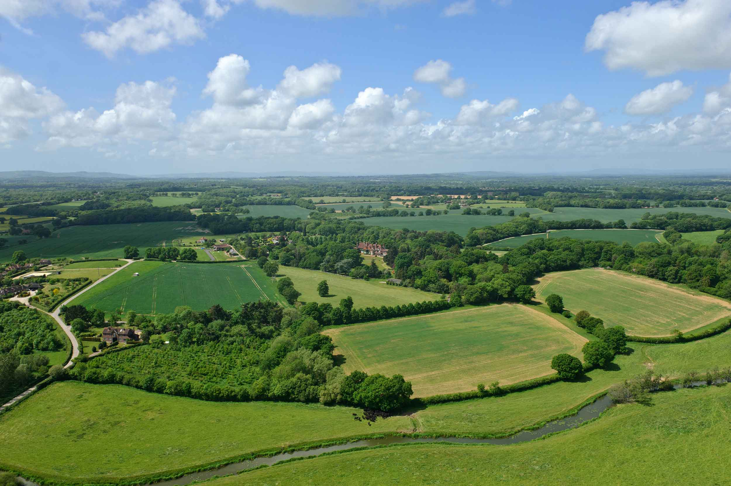 A scene of pastoral splendor: The rolling meadows and verdant woodlands of West Sussex provide a picture-postcard setting for this refuge in the English countryside.