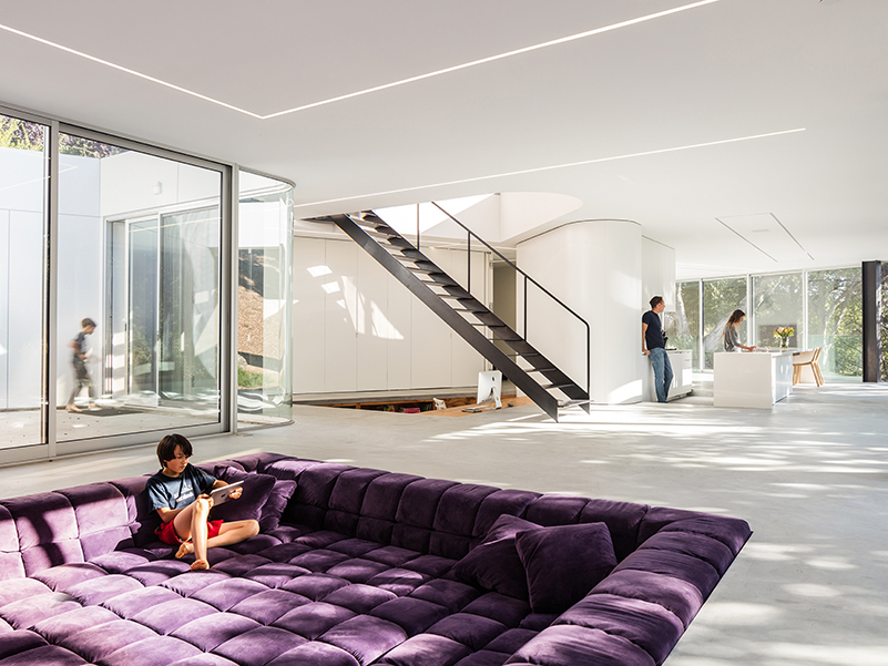 Open-plan living space with purple square sofa