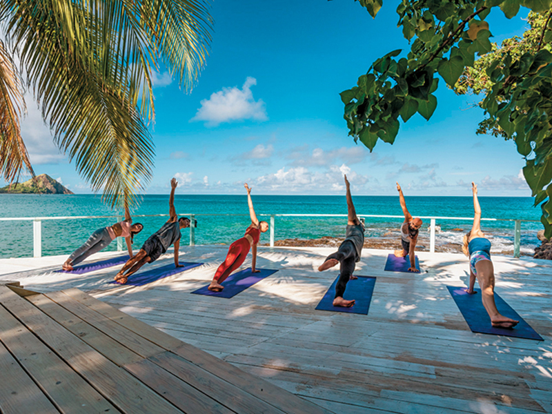 A group doing yoga near to the ocean at BodyHoliday St Lucia
