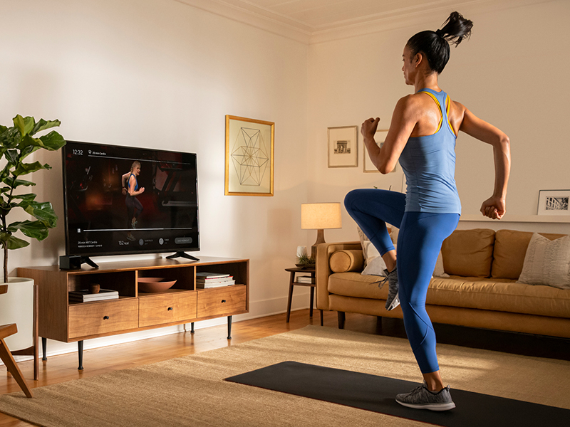 A woman using the Peloton app to take a virtual exercise class