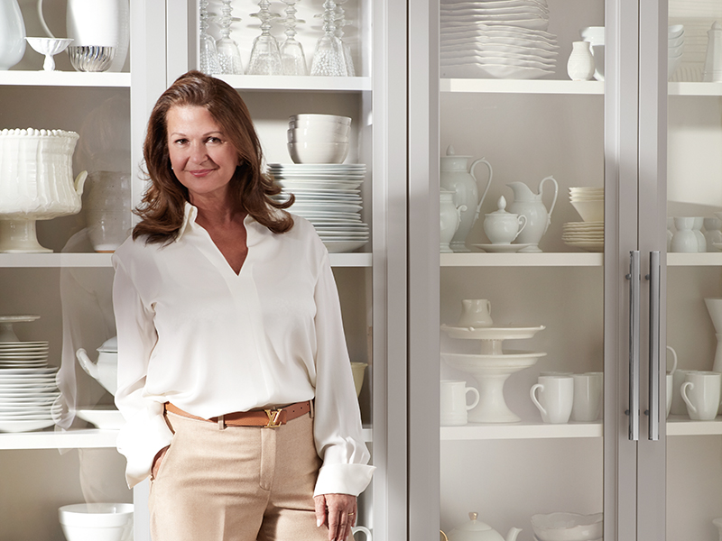 Karen Williams poses in front of a St Charles classic kitchen cabinet