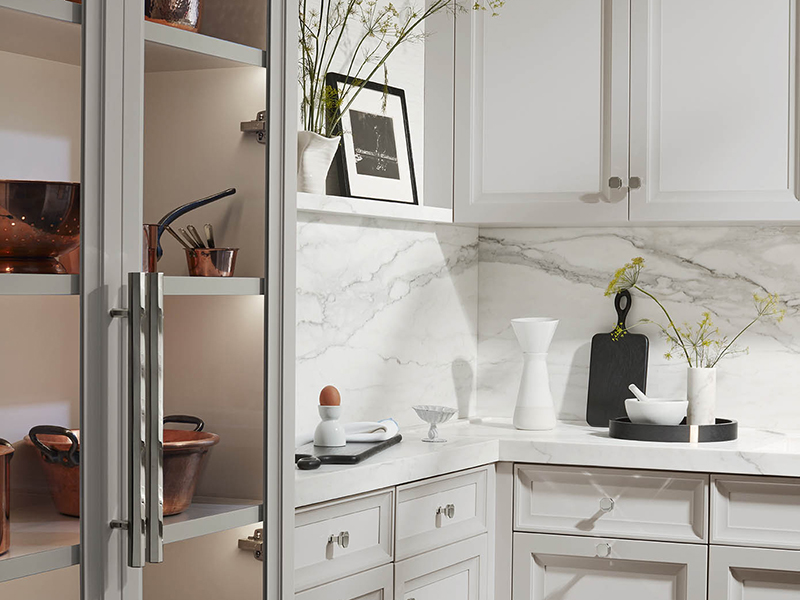 Copper cooking ware is displayed in a white marble kitchen