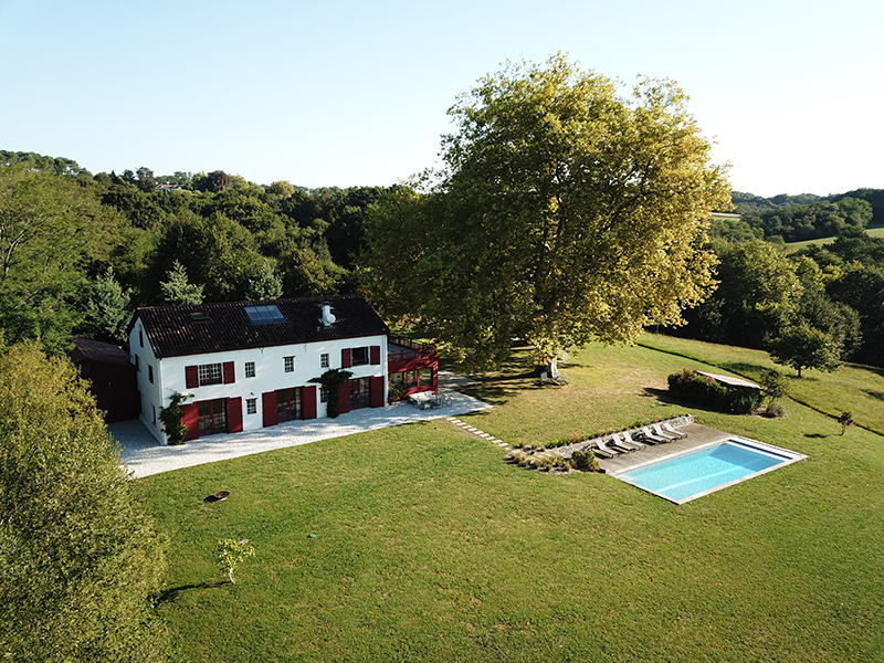 An aerial view of a farmhouse and pool surrounded by lush fields