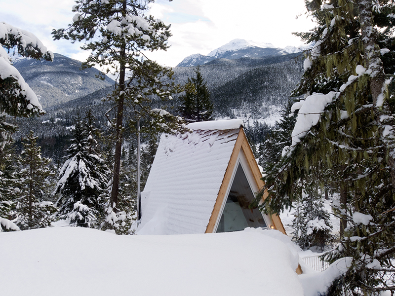 An A-frame cabin surrounded by snowy mountains