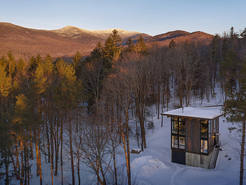 Vermont cabin surrounded by snow, trees and hillside