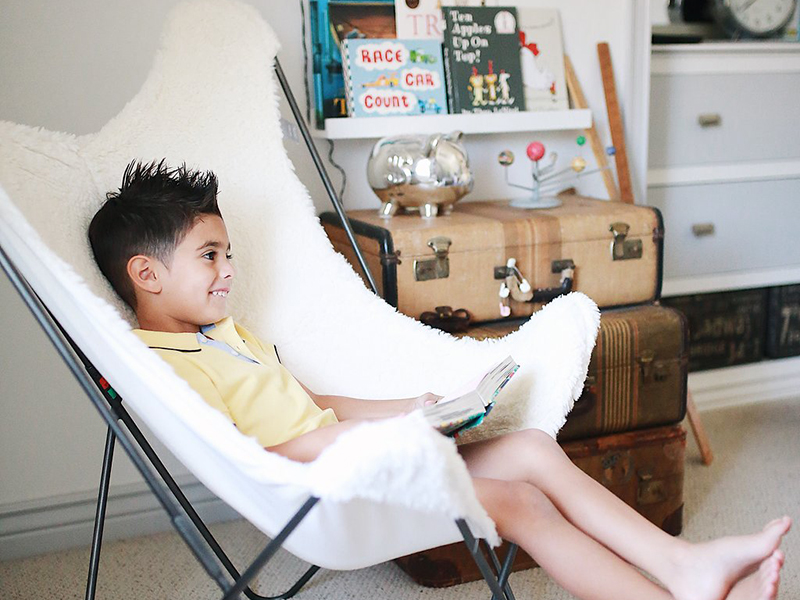 Boy sitting in a comfortable reading nook
