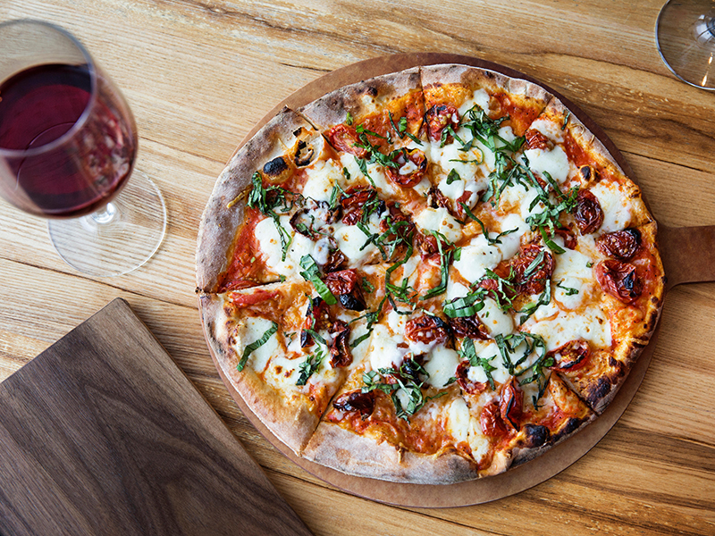 verhead view of fresh pizza with red wineglass