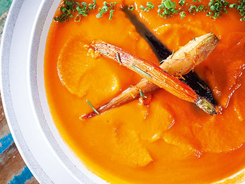 Dish of carrot soup topped with roast carrots