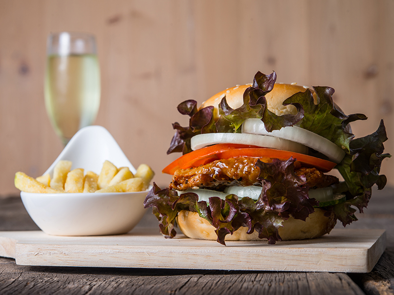 Home made burger with champagne,french fries, lettuce, tomato and onion on wooden board.