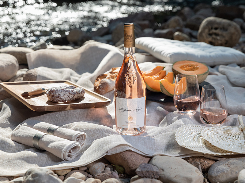 A bottle of Whispering Angel Rose on a picnic blanket next to the river