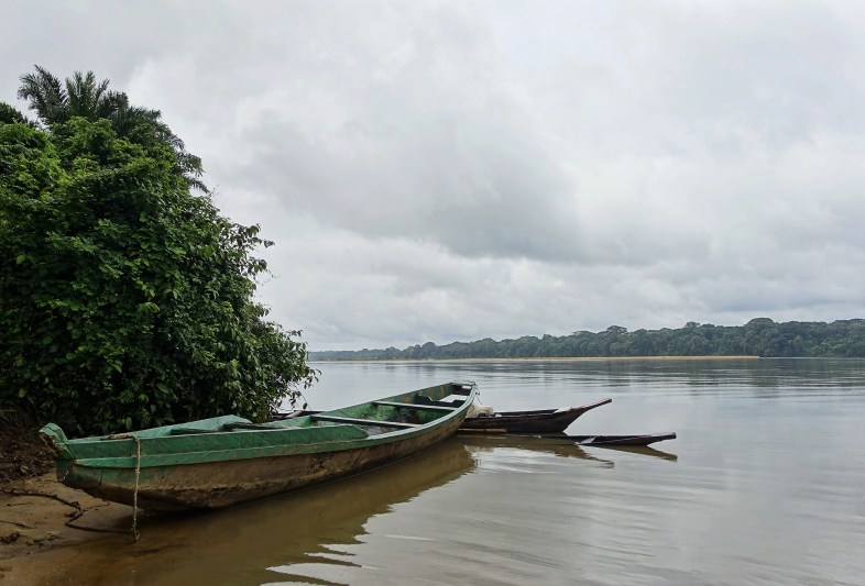 A wooden canoe at the shore of on a brown river and a very cloudy sky