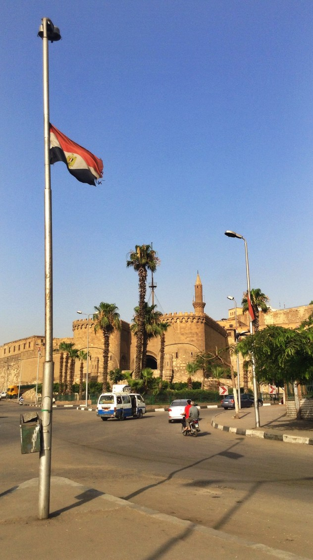 An Egyptian flag blowing in the wind in a traffic circle