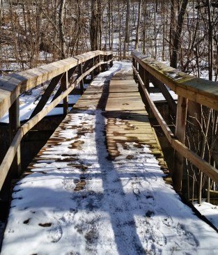 A wooden bridge covered in snow