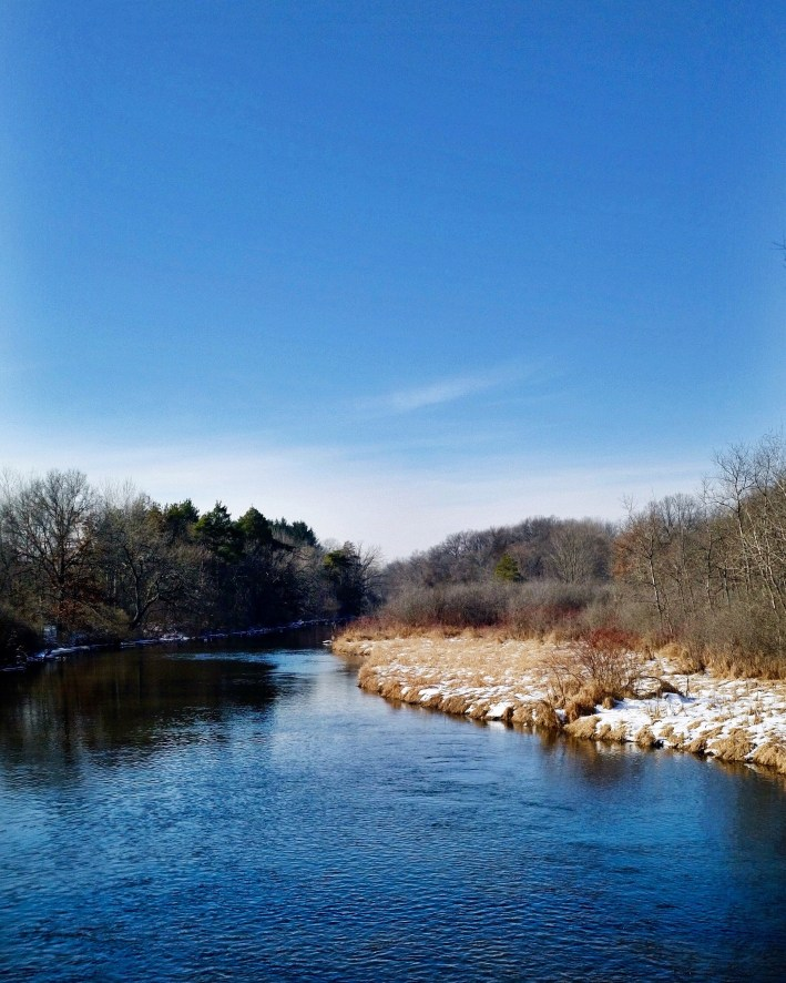 A clear blue sky over a still river with snow on the riverbanks