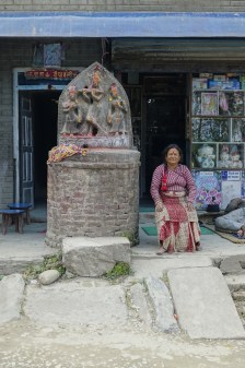 hindu deities carved in a rock in front of a shop with a woman sitting next to it