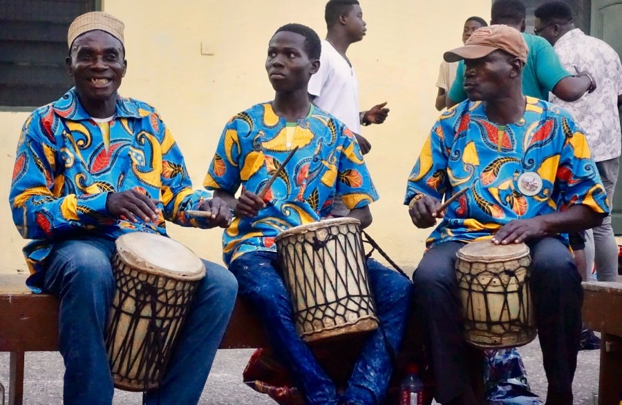 Three men in blue shirts drumming on traditional African drums