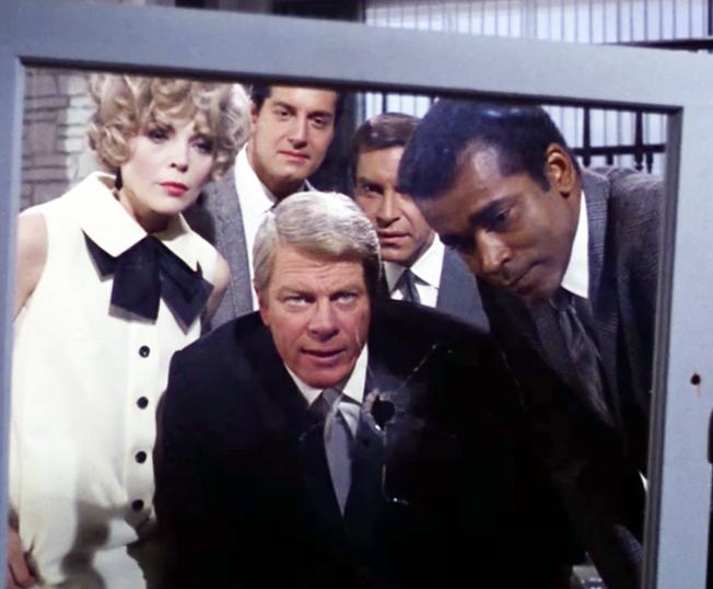 """Phelps (Peter Graves) briefs the team in """"Recovery"""" (with Barbara Bain, Peter Lupus, Martin Landau, and Greg Morris)"""