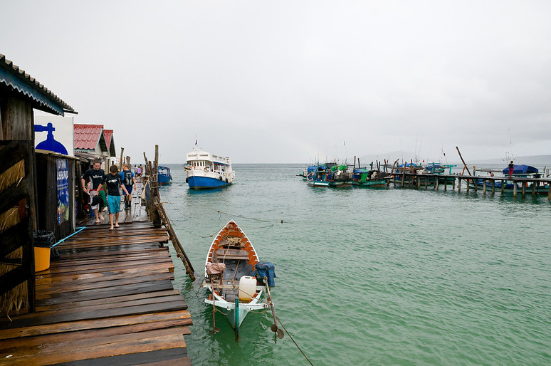 The Dive Shop pier, to the left, can hold upwards of 20 overnight visitors in two rooms. Meals are cooked by local women employed by the Shop and local men are paid to fill air tanks and bring divers to the dive sites. Approaching the pier is the twice-daily ferry, which carries food and tourists the two hours from the mainland.