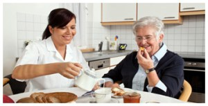 nurse and elderly lady eating at a table