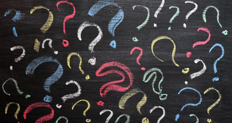 Question marks on a black backboard