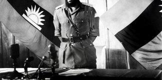 Colonel Chukwuemeka Odumegwu Emeka Ojukwu, the leader of the breakaway Republic of Biafra, stands in front of a Biafra flag