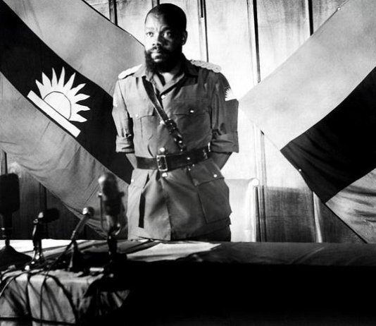 Colonel Chukwuemeka Odumegwu Emeka Ojukwu, the leader of the breakaway Republic of Biafra, stands in front of a Biafra flag