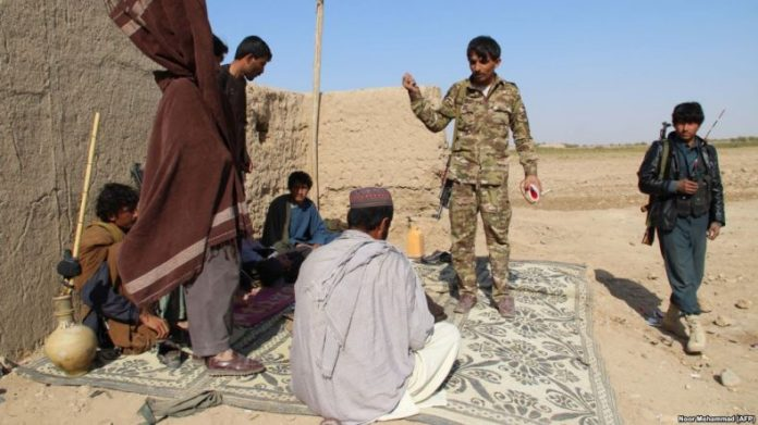 Afghan Local Police officers stand at a checkpoint in Helmand