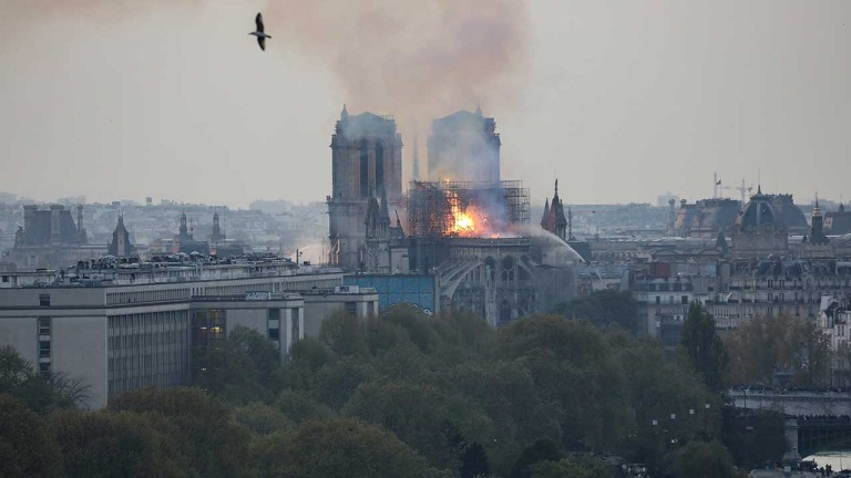 Flames and smoke are seen billowing from the roof at Notre-Dame Cathedral in Paris