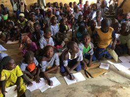 Primary school pupils studying on the floor in Kawu