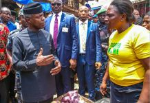 Vice President Yemi Osinbajo interacts with a petty trader in Onitsha, Anambra State
