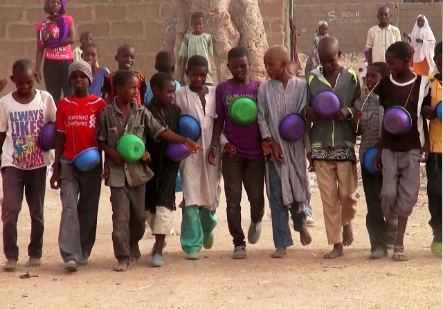 Some Nigerian children begging for alms with bowl in their hands