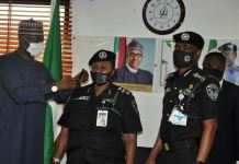 SGF Boss Mustapha decorating a senior police officer as IGP Adamu looks on police commissioners